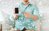 advertisement, people, home and technology concept - close up of man showing smartphone blank screen sitting on couch at home