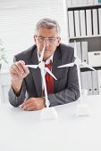 Businessman looking at model wind turbines in his office