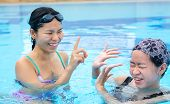 pic of one piece swimsuit  - Two Asian girls are flicking water to one another in the swimming pool with happy expression - JPG