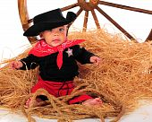 image of baby cowboy  - An adorable biracial cowboy baby sitting in a pile of hay near a large wagon wheel - JPG