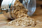 picture of porridge  - rolled porridge oats falling out of a glass jar - JPG