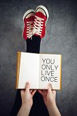 picture of legs air  - You Only Live Once or YOLO Concept with Young Woman Reading Book with Her Feet Raised in The Air - JPG