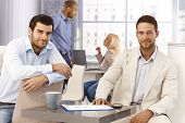 pic of work crew  - Portrait of handsome young businessmen sitting by table - JPG