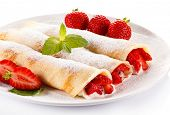 stock photo of crepes  - Crepes with strawberries and cream on white background - JPG