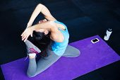picture of yoga mat  - Young woman stretching on yoga mat at gym - JPG