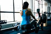 Постер, плакат: Back view portrait of a young woman working out on simulator at gym