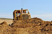 pic of bulldozer  - Large bulldozer moving rock and soil for a fill lift at a new commercial development road construction project - JPG