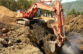 foto of track-hoe  - Large track hoe excavator digging out old rock and soil during preperation at a new commercial development road construction project - JPG