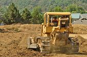 stock photo of bulldozer  - Large bulldozer moving rock and soil for a fill lift at a new commercial development road construction project - JPG