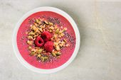picture of granite  - Smoothie bowl with raspberries granola and chia seeds on a white granite background overhead view - JPG