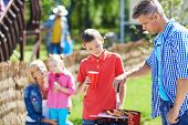 picture of grilled sausage  - Young man frying sausages on grill outdoors with his son near by - JPG