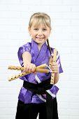 stock photo of karate-do  - Little girl in kimono doing exercises with nunchaku on wall background - JPG