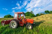 stock photo of hay bale  - Red tractor in a mountain meadow with hay bales handmade - JPG