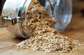 pic of oats  - rolled porridge oats falling out of a glass jar - JPG