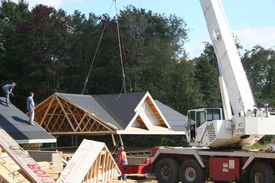stock photo of trussle  - lifting roof of modular home off foundation to proceed building walls and second floor and then will be put back on - JPG