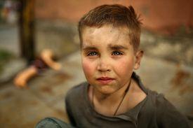 stock photo of sad  - alone sad child playing on a street - JPG