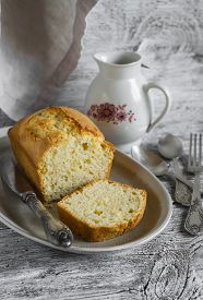 stock photo of milkman  - simple cake on an oval plate milk jug and silver cutlery on a light wooden background - JPG