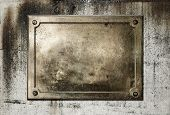 Brass yellow metal plate on grungy concrete background texture