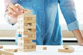 Постер, плакат: Hand Of Engineer Playing A Blocks Wood Tower Game jenga On Blueprint Or Architectural Project