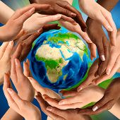 Beautiful conceptual symbol of the Earth globe with multiracial human hands around it. Unity and wor