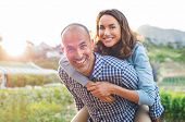 Happy mature couple enjoying outdoors during sunset. Smiling woman piggyback on her man while lookin poster