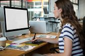 Female graphic designer using graphics tablet at desk in office poster