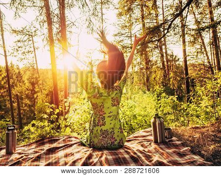 poster of Beautiful Young Girl With Open Arms Sitting On A Plaid In A Forest Glade During Sunset Bright Sunlig