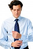 Corporate worker adjusts his cufflinks as his last step before heading to work