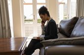 Side view of a female  African American real estate agent talking on mobile phone while using digita poster