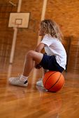 Low angle view of a mixed -race  schoolgirl sitting on a basketball on basketball court at school poster