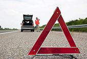 Road side warning triangle, warning oncoming traffic of a broken down car, with a man using his cell