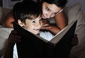 Boy and girl reading light book at night, children concept