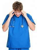 Nurse / doctor headache and stress. Stressed young male medical professional in blue scrubs touching