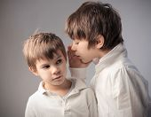 Child telling a secret to his brother