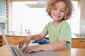 Junge mit einem Laptop in einer Küche