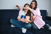 Beautiful Brunette Caucasian Mother And Daughter Sit Together In Room. Mom Covered Eyes Of Girl. She poster