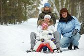 foto of toboggan  - Happy kids and their parents tobogganing in park - JPG