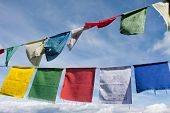 Buddhist tibetan prayer flags flying in the wind against blue sky