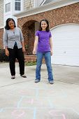 foto of hopscotch  - Child playing hopscotch outside at her home - JPG