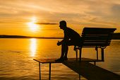 Silhouette Of A Man Sitting On The Bench In A Bridge And Looking At Beautiful Orange Sunset. Single  poster