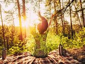 Beautiful Young Girl With Open Arms Sitting On A Plaid In A Forest Glade During Sunset Bright Sunlig poster