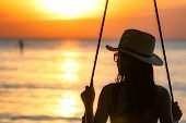 Silhouette Woman Wear Bikini And Straw Hat Swing The Swings At The Beach On Summer Vacation At Sunse poster