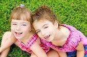 Постер, плакат: дети девочки смеясь сидя на зеленой траве парк