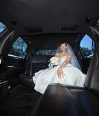 Attractive bride sitting in limousine holding flower bouquet