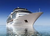pic of passenger ship  - luxury white cruise ship shot at angle at water level on a clear day with calm seas and blue sky - JPG