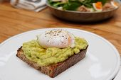 Toast with guacamole and poached egg, breakfast dish poster