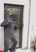 Burglar breaking door from outside with crow bar