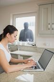 Woman using laptop in kitchen with robber looking at her through window