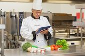 picture of scallion  - Chef preparing recipe with digital tablet in the kitchen - JPG