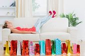 Woman lying on the sofa behind a row of bags tired after shopping